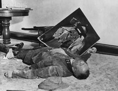 A general of the Volkssturm lies on the floor of city hall in Leipzig, Germany with a torn picture of the fuehrer, after committing suicide rather than face U.S. Army troops who captured the city on April 19, 1945.