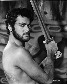 this gorgeous brooding man is Tony Curtis, a Hollywood actor whose career spanned almost 6 decades and 100 films. He was very big in the 1950s and early 1960s. He was in The Odd Couple, The Vikings (pictured here) and he was also in Some Like it Hot with Marilyn Monroe…