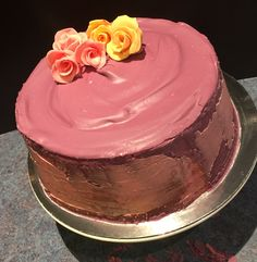 Strawberry and vanilla sponge with chocolate filling, purple, pink and chocolate Neapolitan icing topped with hand made fondant roses. By Natalie Baxter