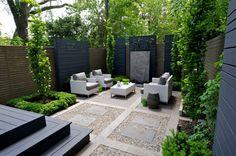 Kleiner Garten mit formaler Gestaltung und Rattan-Sitzgruppe