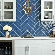 The blue ceramic backsplash tile is a much needed field of color in this white kitchen. The herringbone pattern is immaculately centered between the cabinets and above the stove. A simple golden chandelier is the perfect finishing touch. A perfect design. Colourful Kitchen Tiles, Blue Kitchen Tiles, Backsplash Kitchen White Cabinets, Stove Backsplash, Blue Backsplash, Herringbone Backsplash, Blue Tiles, Herringbone Pattern, Backsplash Ideas