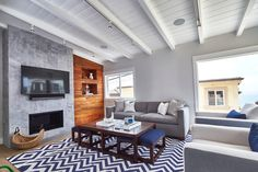 Coffee table with stools, blue & white rug, wood wall (does it have hidden drawers?).  Projects | Noelle Interiors