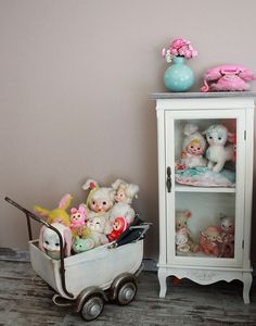 A small medicine cabinet with glass door and a baby-doll stroller is good way to display vintage toys.