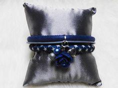 Een leuke dubbele armband in het blauw. De armband bestaat uit meerdere delen die samen worden gehouden door middel van een ring met daaraan leuke bedeltjes. De armband bestaat uit de kleuren donkerblauw, grijs en een bandje in het blauw met witte sterren. Aan de ring hangen bedels zoals een hartje, kralen en een blauwe roos.
