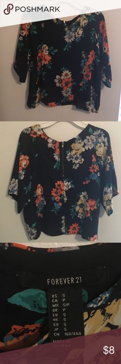 Floral top! This top contains a zipper in the back and has a bunch of beautiful colors all over it! I only wore it once and it's so comfortable and flowy! Forever 21 Tops Blouses