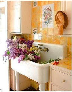 Vintage kitchen sink in a utility room filled with lilacs......