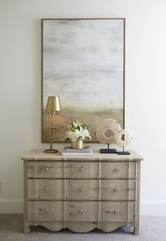 Chic foyer features a 3 drawer scalloped dresser topped with an antique brass task lamp placed under a blue and gold abstract art piece.
