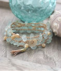 Aqua sea glass pieces man-made from recycled glass with faceted mother of pearl beads crocheted with a tan cord. A handmade…
