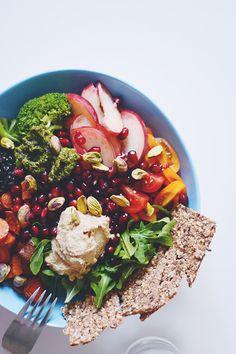 ruccola, tomater, dampet  broccoli, ovnstegte søde kartofler og gulerødder, belugalinser, fersken, granatæblekerner, hummus, pesto, usaltede pistacienødder og hørfrøknækbrød.