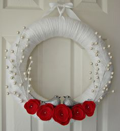 white yarn wrapped holiday wreath with red felt flowers and pearl berries.