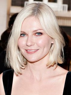 Kirsten Dunst angled, bleach blonde bob hairstyle with defined eyelashes and a rosy complexion | allure.com