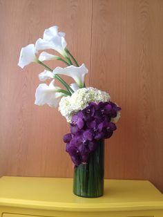 Copo de leite, hortênsia branca e wandas em um arranjo floral estruturado e elegante.