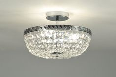 art. 85638 Bijzondere plafondlamp van chroom en kristallen (kristalglas). De draden met kristallen hangen tussen de buitenrand en de afsluitdop in het midden van de lamp in een soort tulbandvorm. De kristallen worden steeds kleiner naarmate ze meer naar binnen hangen.http://www.rietveldlicht.nl/artikel/plafondlamp-85638-klassiek-retro-chroom-kristal-kristalglas-metaal-rond