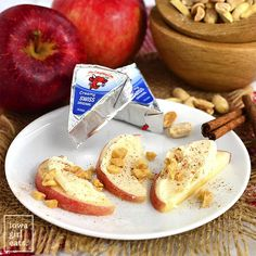 Laughing cow Swiss cheese on Apple slices sprinkled with cinnamon and peanuts.