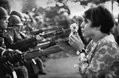 """La Jeune Fille a la Fleur,"" a photograph by Marc Riboud, shows the young pacifist Jane Rose Kasmir planting a flower on the bayonets of guards at the Pentagon during a protest against the Vietnam War on October 21, 1967. The photograph would eventually become the symbol of the flower power movement."