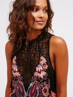 Lightweight printed slip featuring a high neck with a sheer delicate lace and scalloped trim. Opening in back with a button closure.