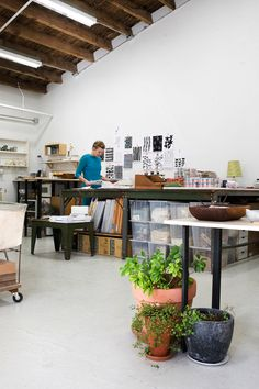 Lotta Jansdotter's studio  -white and wood and high ceiling  -huge work surface with storage underneath  -from DesignSponge