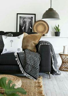 Un tapis en toile de jute, un pouf tressé, de gros coussins aux couleurs foncés dans canapé gris foncé, plus une jetée.