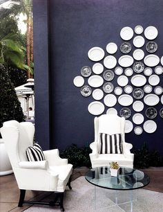 Patio with dark blue walls, white wing chairs and an arrangement of various plates on the wall.
