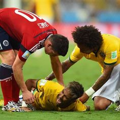 Neymar writhes in agony after injuring his back - Neymar of Brazil lies on the field after a challenge as teammate Marcelo and James Rodriguez of Colombia look on during the 2014 FIFA World Cup Brazil Quarter Final match between Brazil and Colombia at Castelao on July 4, 2014 in Fortaleza, Brazil.  i love how james is helping