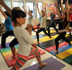 Christina Lowden, left,  co-owner of Trinity Yoga Studios, shows students how to do a warrior I pose (Virabhadrasana), which helps to stretc...