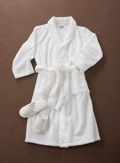 Bath Robe and Slippers Set - No trip to the spa is complete without a cozy cotton robe and slippers. Whether fresh from the shower or relaxing on a weekend morning, our set is a perfect touch. Kimono-style, unisex robe has two roomy pockets and an easy sash belt. One size fits most. 100% cotton in white. Made in Portugal.