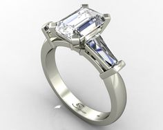 Emerald cut trilogy ring with tapered baguette cut diamonds.