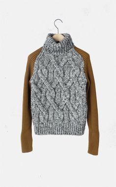 grey cable sweater with camel ribbed long sleeves.