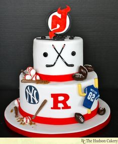 A two-tier cake featuring several sports logos, but the Devils logo is the topper!