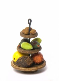 The handmade miniature wooden three-tiered stand in dark nut brown fits perfect to every dollhouse kitchen. The plates can be filled with fruits, vegetables, cookies etc. Measurements: Height: 5.4 cm / 2.13 inch Diameter small plate: 1,5 cm / 0.59 inch Diameter medium plate: 2,0 cm / 0.79 inch Diameter large plate: 3,0 cm / 1.18 inch  Dollhouse scale 1:12.  IMPORTANT: The price is for one tree-tiered stand. I added more stands and fruits for illustration only.