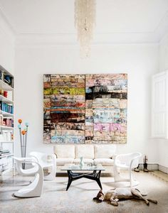 White living space with large eclectic art and dog