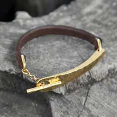 "Require Bracelet in Chocolate and Brass, $65. A thin leather bracelet features a polished, textured bar toggle closure. The smooth leather matched with the polished hardware makes for a perfectly put together wrist. Fits up to 6.5"" wrist."