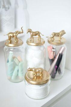 Frascos para organizar el baño. Las tapas de los frascos tiene animalitos plásticos pegados y pintados con spray dorado.