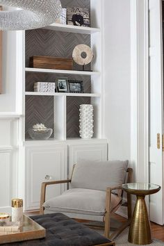 A light gray velvet chair sits on a gray rug between an Ernest Mira Table and a styled built-in shelves accented with gray herringbone wallpaper and white cabinets. Grey Herringbone Wallpaper, Grey Chevron Wallpaper, Grey Wallpaper Accent Wall, Gray Chevron, Wall Wallpaper, Wallpaper Fireplace, Wallpaper Bookshelf, Built In Shelves Living Room, Grey Bookshelves