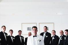 Groom in white, guys in black