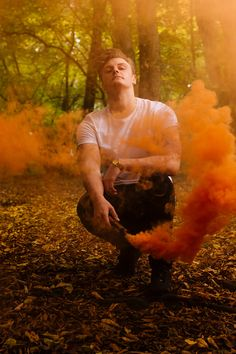Nate Vaughan Photography - SMOKE - male model in the woods with orange smoke bombs.