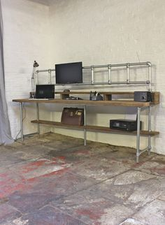 Reclaimed Scaffolding Board Industrial Style Desk with Built In Storage Section, Overhead Monitor Mounting Rails and Under Shelf - works perfectly in a sophisticated urban casual living space. This desk can be made to measure to your own specifications. The item pictured here is 630mm deep, 2400mm wide and 1312mm high... but the skys the limit... please contact us to discuss any ideas or obtain quotes. The 33mm galvanised steel legs have little plastic caps fitted on the bottom so they…