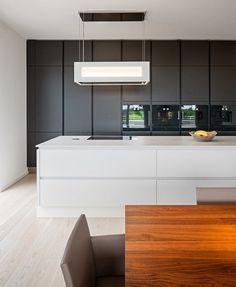 Weiße Kochinsel und schwarze Kronleuchter in einer modernen Küche ...