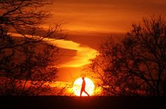 A man walks on top of the flood wall in Newport, Ky., Wednesday morning, March 21, 2012 as the sun rises behind him. (AP Photo/The Enquirer, Carrie Cochran)  CARRIE COCHRAN - AP