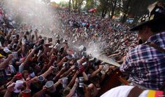 Visitors try to fill their mugs as beer is sprayed on them from a barrel at Argentina's Oktoberfest, the national beer festival, in Villa General Belgrano, Argentina, Oct. 9, 2016.