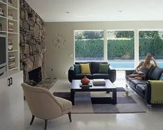 The new 1960s signature stacked-stone fireplace reaches the vaulted ceiling and is flanked by new built-in bookshelves. The sliding door and fixed-glass panels were reversed for better traffic flow from the pool area into the house.