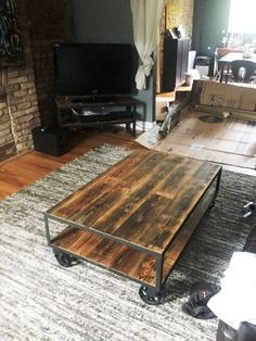 This is a vintage industrial style coffee table on 5 swivel casters with brakes, measuring approximately 48W x 16H x 30D. Recycled 1 square metal tubing is used for the frame and reclaimed barn wood is used for the top and shelf. The metal has a matte black finish and the wood is sealed with a satin polyurethane. We can make this in any size you need and we can also run the boards the short way if you prefer, and we can use different finishes on both the metal and wood. Let us know what you…