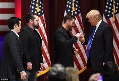 Three veterans give Trump, right, a 22 Kill Honor Ring that represents twenty veterans that kill themselves daily by suicide during a rally on the Drake University campus at a special event to benefit veterans on Thursday