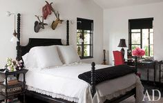 In the master bedroom, the four-poster is by Jayson Home & Garden, with white linen bedding by Matteo.