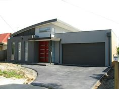 Grey rendered house with feature door - monument roof and garage door