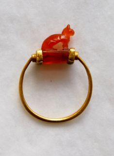 An ancient Egyptian gold finger-ring, with a carnelian bezel in the form of cat, symbol of the goddess Bast/Bastet, with a wedjat-eye on the under side.