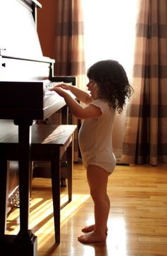 Too cute! :) She looks like she's happy to finally be able to reach the piano keys.