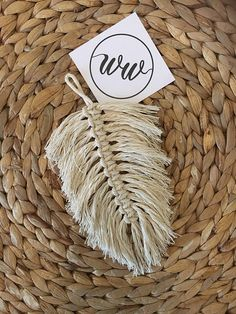 Beautifully handcrafted small macrame feather, 100 percent cotton, use as a wall hanging or lay on a surface to display 17cm long by 10cm wide
