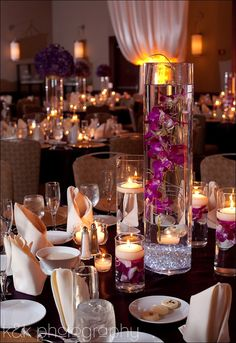 The centerpieces will be tall cylinder vases with large, submerged purple cymbidum orchid stems lit up from below with white LEDs (no floating candle on top) surrounded by three skinny cylinders at varied heights with floating green spider mums inside the vases and three clear votives.