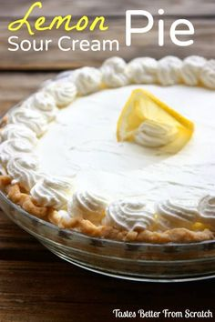 A beautiful lemon sour cream pie in a clear dish with whipped cream piped around the edges and a sliced lemon in the center.